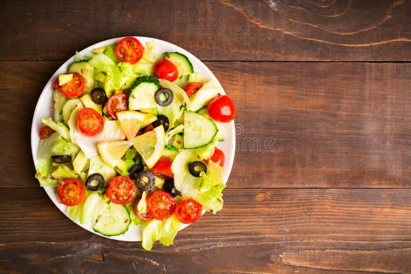 绿色和红色沙拉平的位置用柠檬和种子在木背景 免版税库存图片