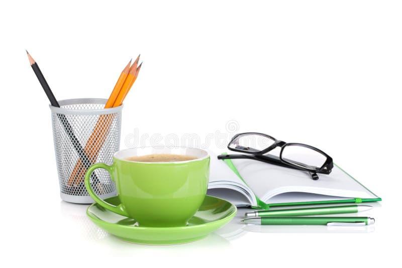 绿色咖啡杯、玻璃和办公用品 库存照片