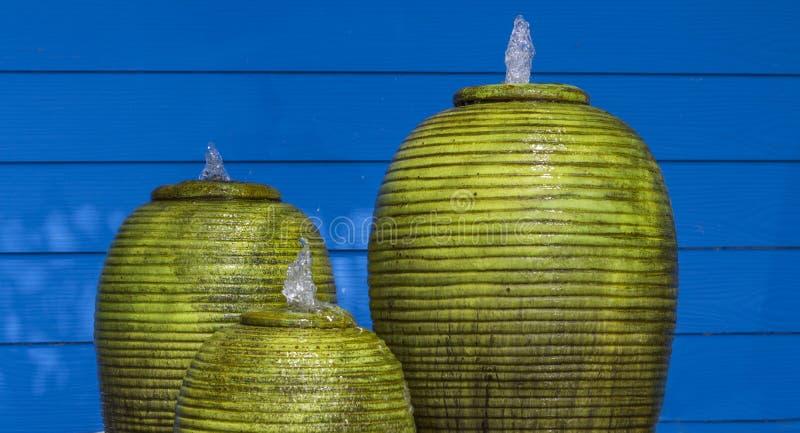 绿色喷泉平安瓶子和蓝色的墙壁 图库摄影