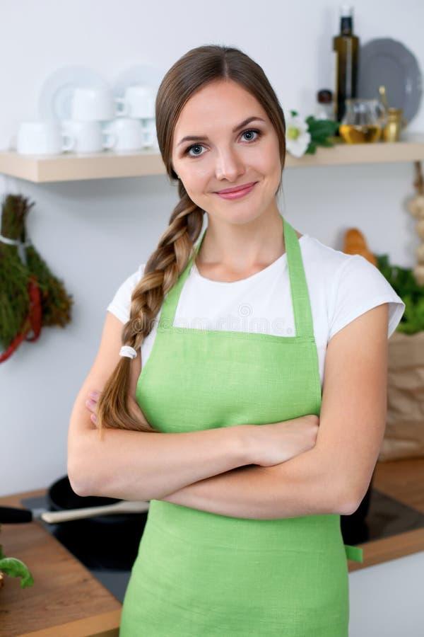 绿色围裙的少妇向烹调求助在厨房里 免版税库存图片