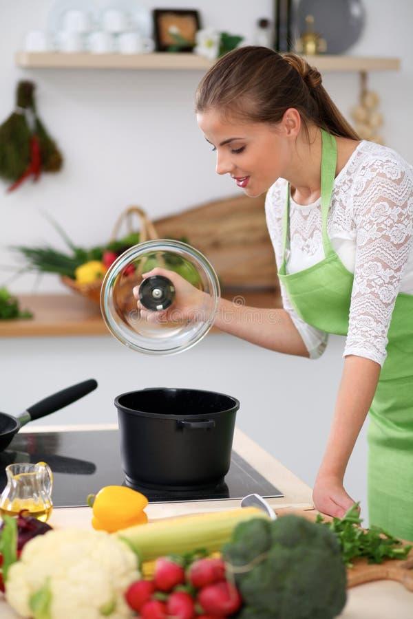 绿色围裙的少妇在厨房里烹调 主妇由木匙子品尝汤 库存图片