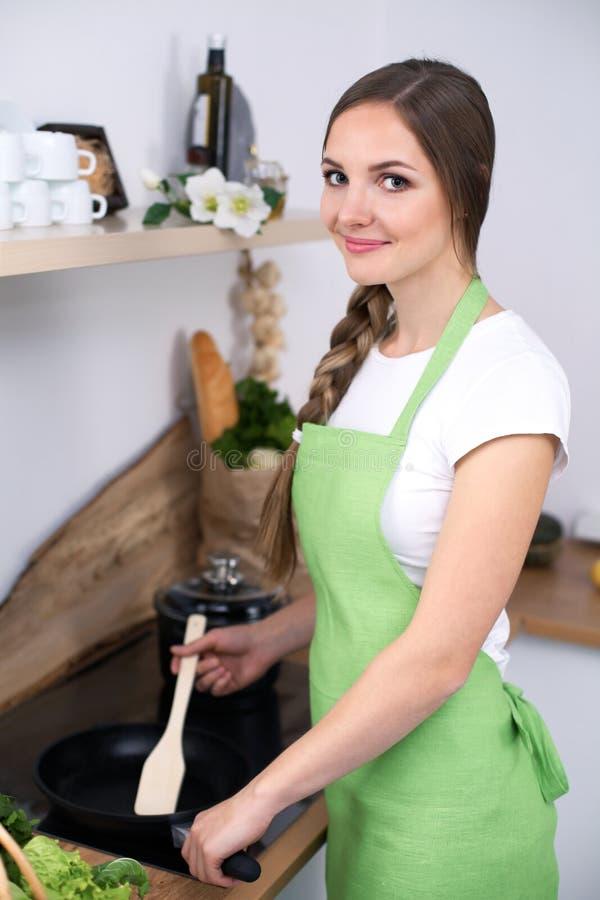 绿色围裙的少妇在厨房里烹调 免版税库存照片