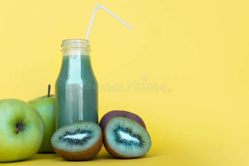 绿色圆滑的人和成份 在瓶的自然,有机健康汁液在与拷贝空间的黄色背景 免版税图库摄影