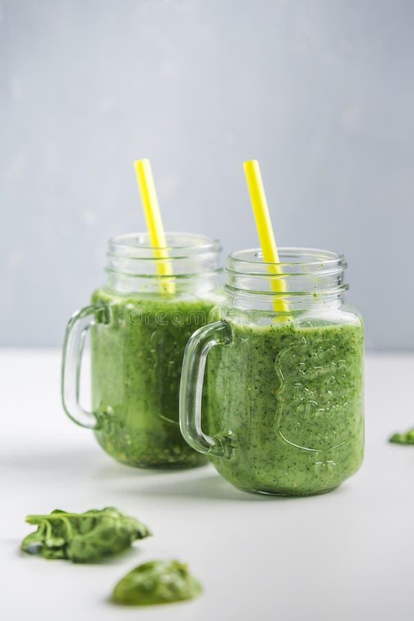 绿色圆滑的人用菠菜、苹果计算机、黄瓜和椰奶 库存照片