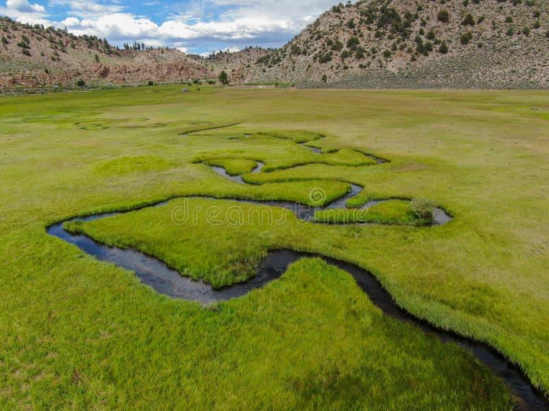 绿色土地和小曲线河空中顶视图有山的在背景中 免版税库存图片