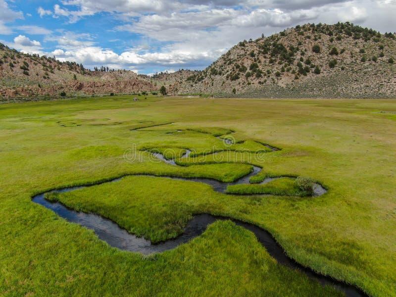 绿色土地和小曲线河空中顶视图有山的在背景中 免版税库存照片