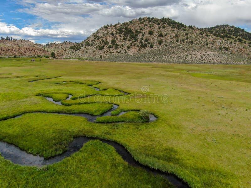 绿色土地和小曲线河空中顶视图有山的在背景中 图库摄影