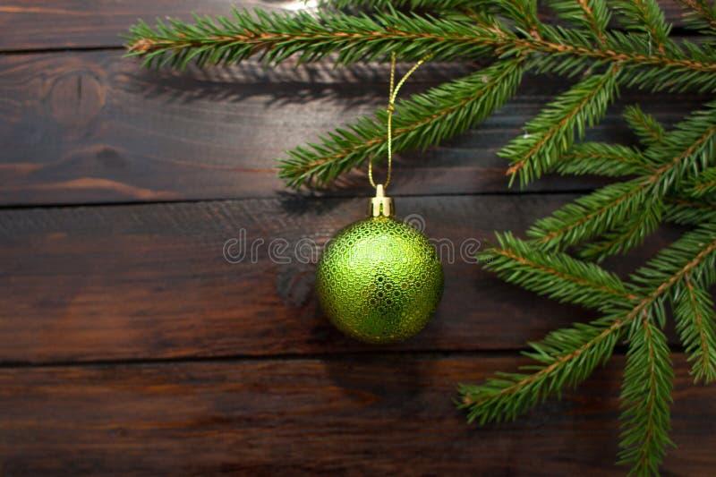 绿色圣诞树在黑暗的木背景分支 与一个绿色玻璃球的新年背景 顶视图 库存图片