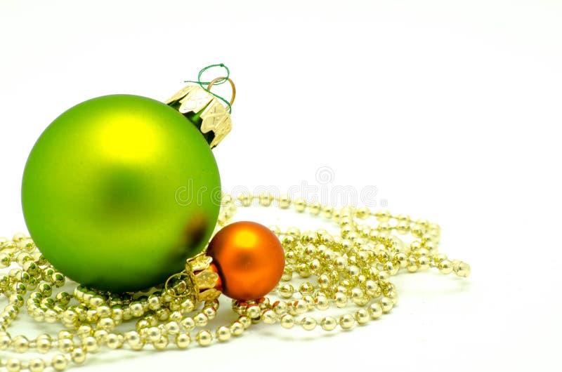 绿色圣诞节的装饰品-和与金黄珍珠的橙色球 库存图片