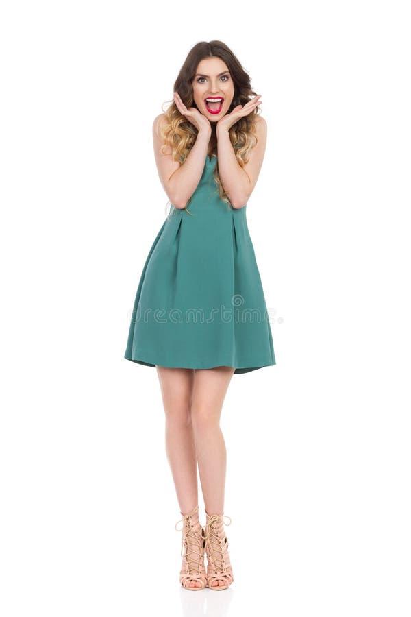 绿色套衫连超短裙和高跟鞋的愉快的美丽的少妇对负顶头在手和呼喊上 免版税库存照片