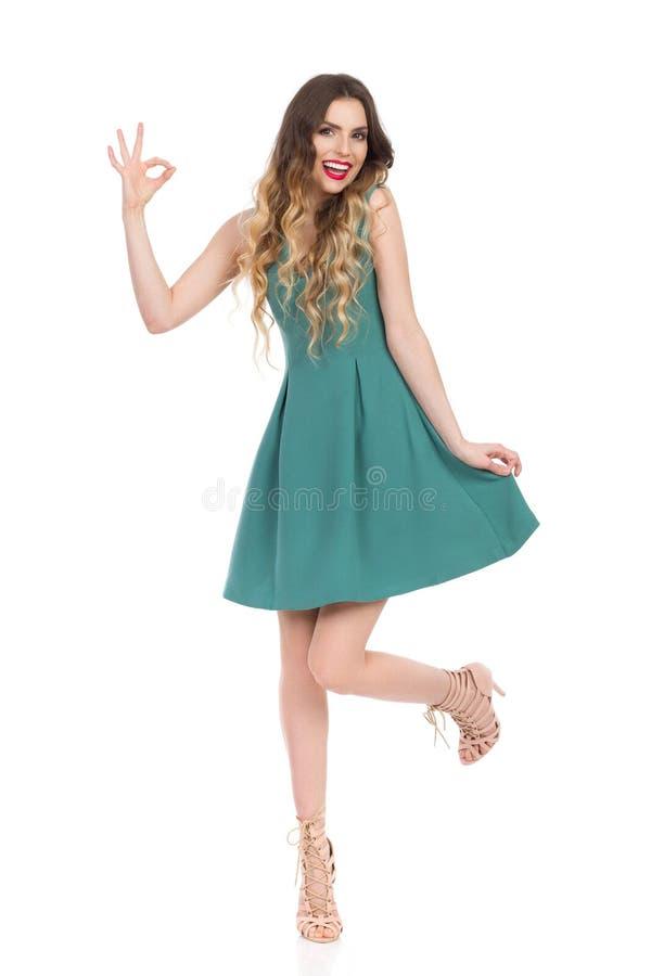 绿色套衫连超短裙和高跟鞋的美丽的少妇显示好手标志和微笑 库存照片
