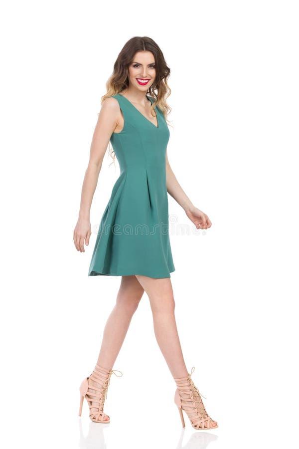 绿色套衫连超短裙和高跟鞋的美丽的少妇走并且微笑着 库存图片
