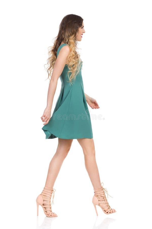 绿色套衫连超短裙和高跟鞋的美丽的少妇走 侧视图 库存图片