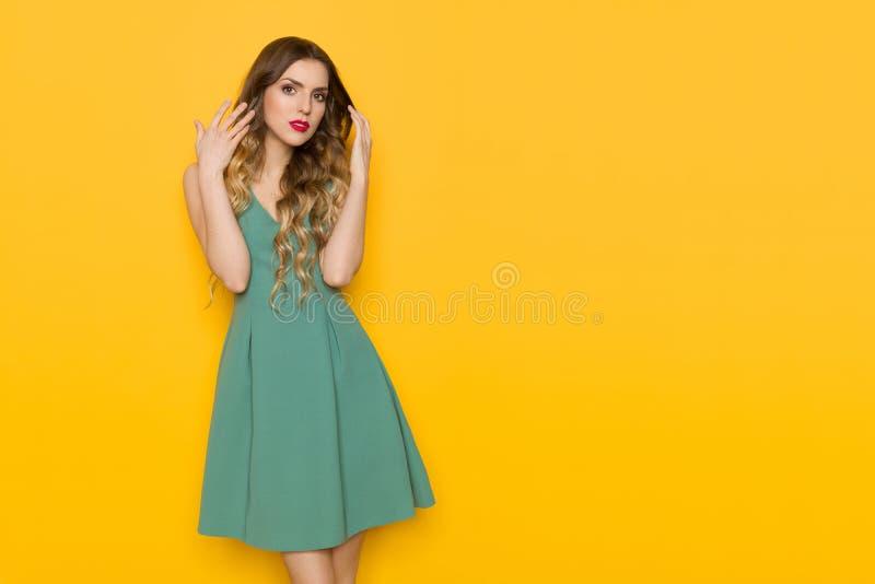 绿色套衫连超短裙的严肃的美丽的妇女 免版税库存图片