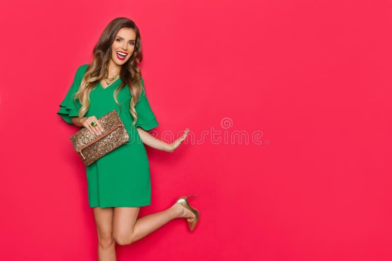 绿色套衫连超短裙的美丽的年轻女人在一腿和笑站立 图库摄影