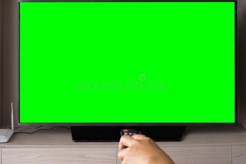 绿色屏幕电视用遥控defocused的手对负 图库摄影