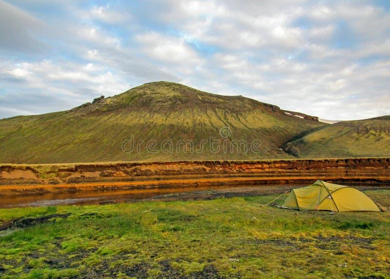 绿色帐篷在有绿色山的在背景中,Alftavatn露营地,Laugavegur,冰岛河旁边投了 库存图片