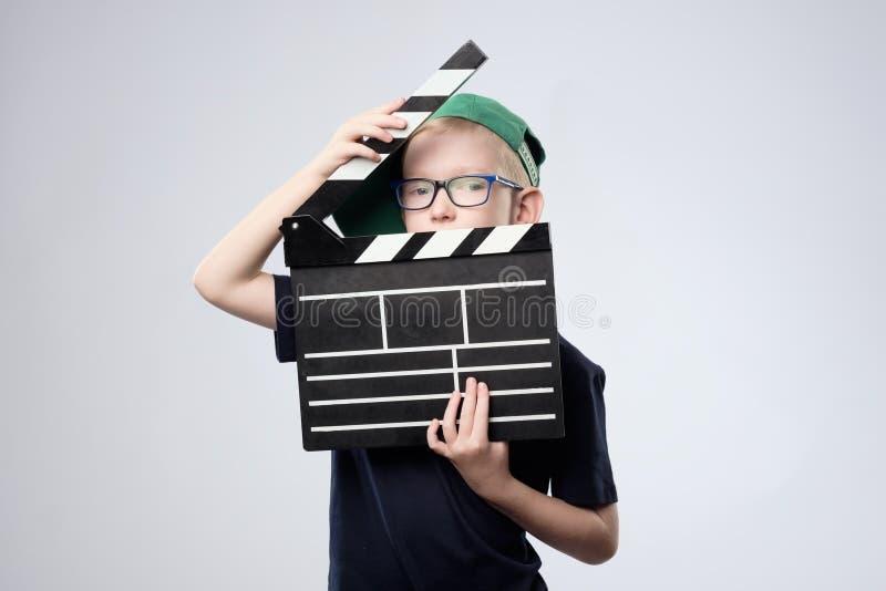 绿色帽子的男孩在手上的拿着拍板 图库摄影