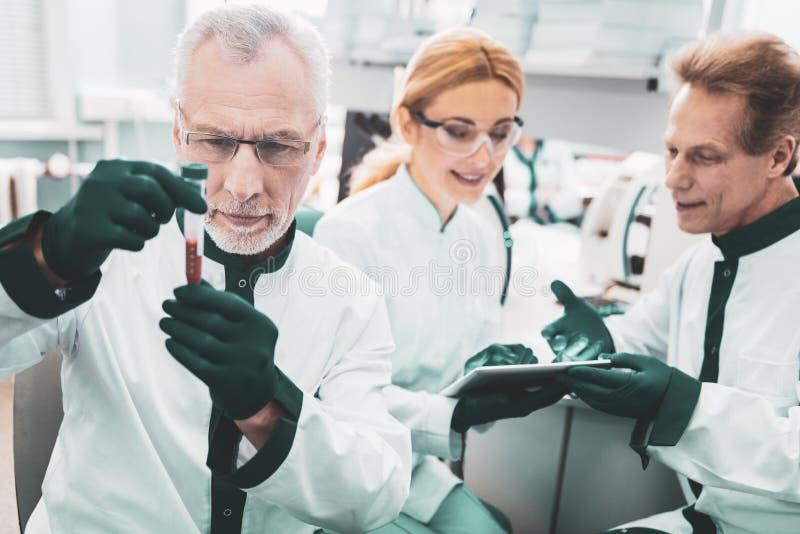 绿色手套的三位科学研究员 免版税库存照片