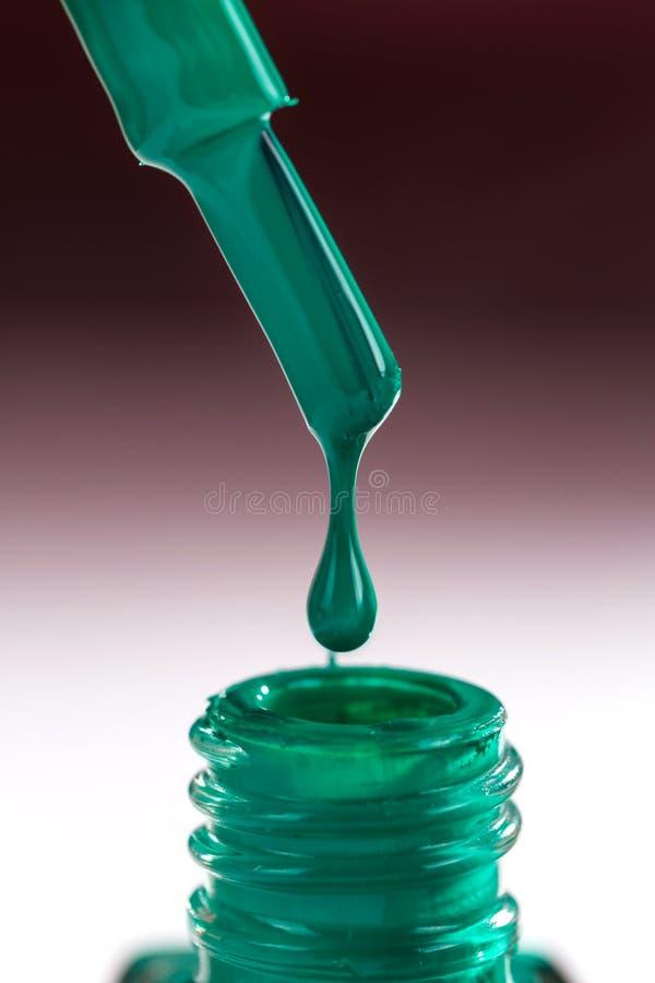 绿色指甲油下落在一把刷子的在一个开放瓶 库存图片