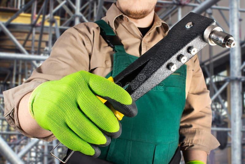 绿色整体成套装备的工作者有铆钉工具的 库存图片