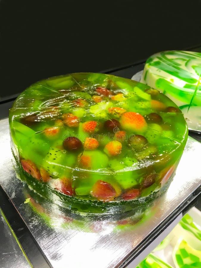 绿色新鲜的热带水果饼果冻以果子选择品种,苹果、葡萄、桃子、草莓和龙结果实 免版税库存照片