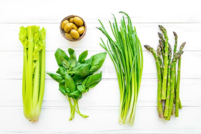 绿色新鲜的草本和菜在白色木背景 平的位置, eco素食主义者背景 库存图片