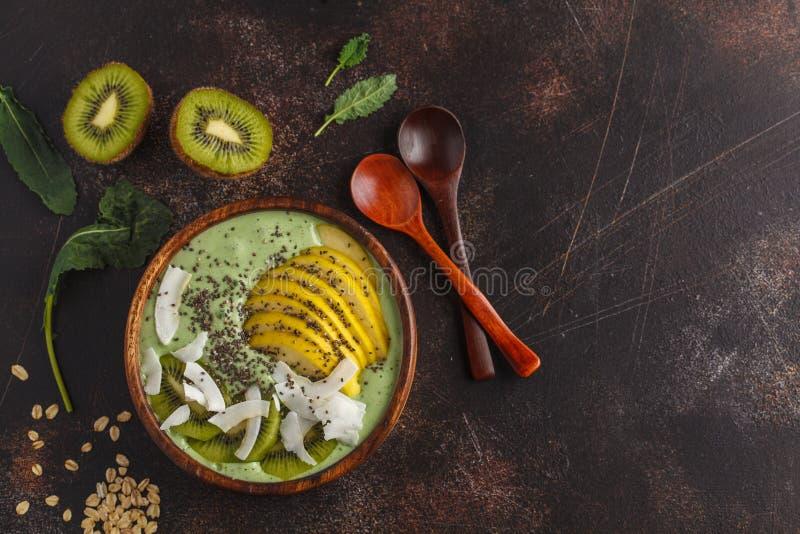 绿色无头甘蓝素食主义者圆滑的人碗用椰子、chia、苹果和kiw 库存照片