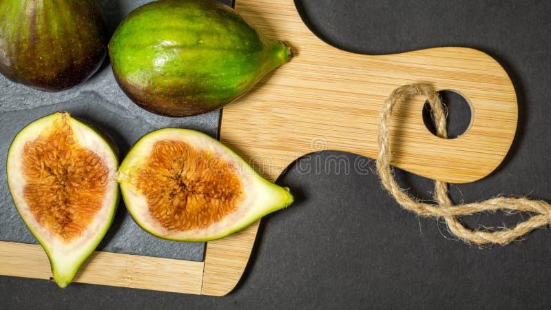 绿色无花果,一果子被切成两个一半和两个整体在木板有木把柄的,黑暗的背景,看法从 免版税库存图片