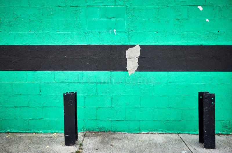 绿色有黑条纹的被绘的砖墙 库存照片