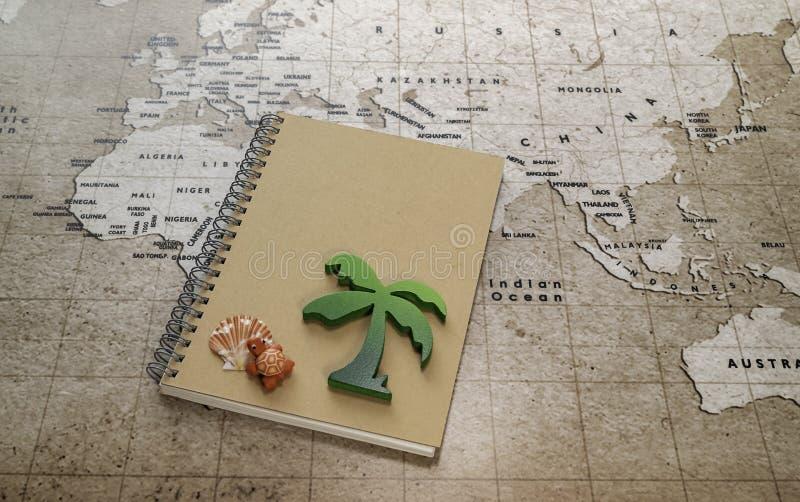 绿色木棕榈树和红色乌龟与海壳在笔记本在世界地图 免版税库存照片