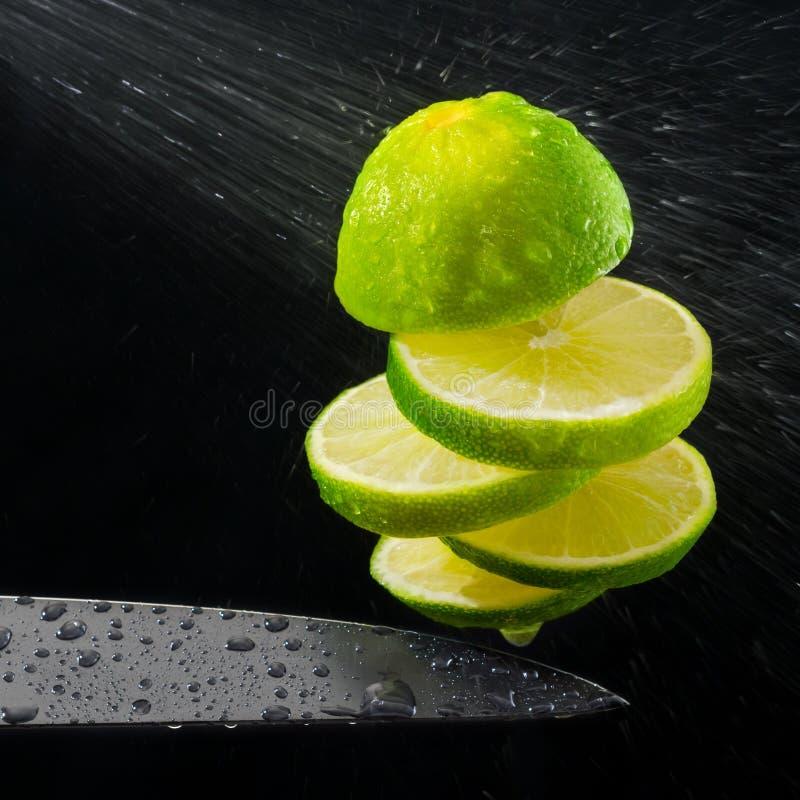 绿色柠檬正在进行中切开了,喷水 免版税图库摄影