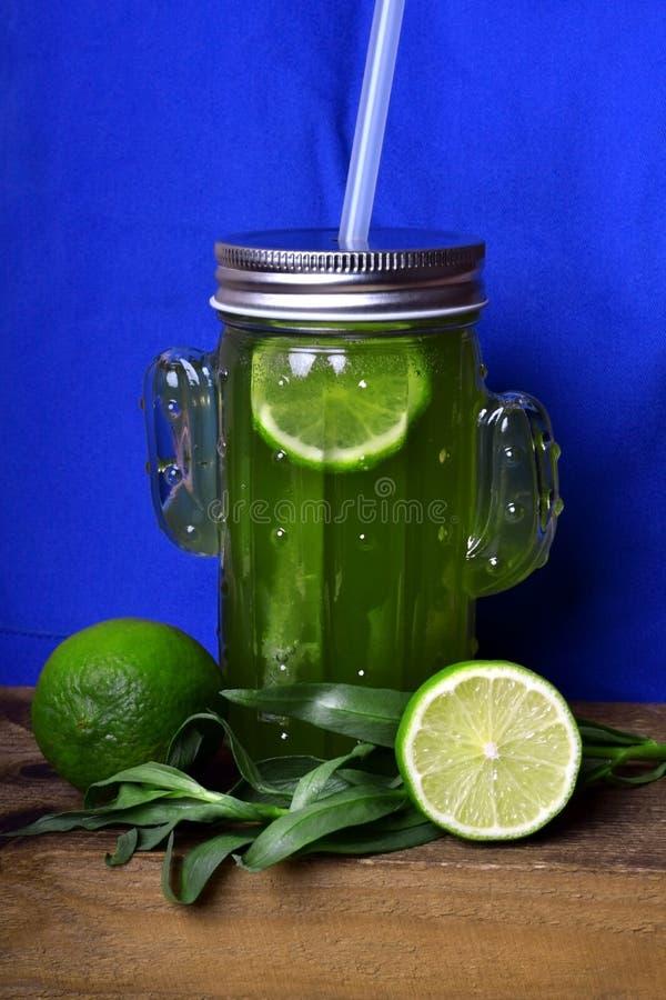 绿色柠檬水用龙篙和石灰在一个玻璃瓶子 库存照片