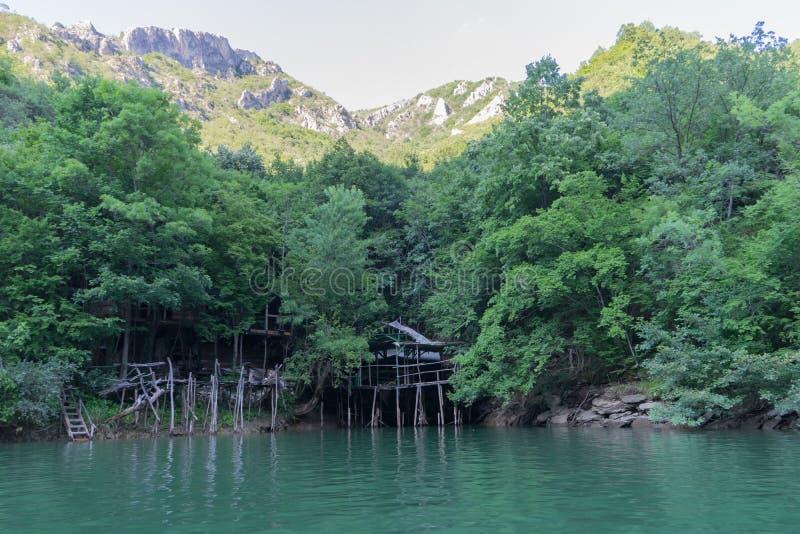 绿色森林的木传统房子里面和山和湖 马特卡峡谷在有大岩石和峰顶的马其顿与 免版税库存照片