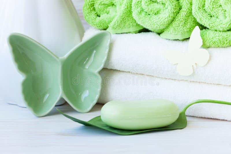 绿色植物叶子、蝴蝶小雕象、软肥皂、花瓶和毛巾 温泉、秀丽和健康沙龙的概念 接近的照片 库存照片