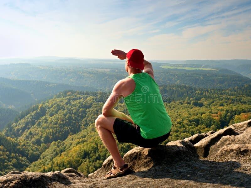 绿色汗衫的亭亭玉立的身体远足者和黑短裤坐岩石,享受自然风景 看法到森林谷里 库存照片
