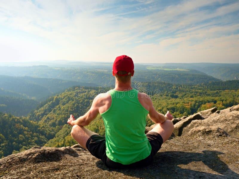 绿色汗衫的亭亭玉立的身体远足者和黑短裤坐岩石,享受自然风景 看法到森林谷里 图库摄影