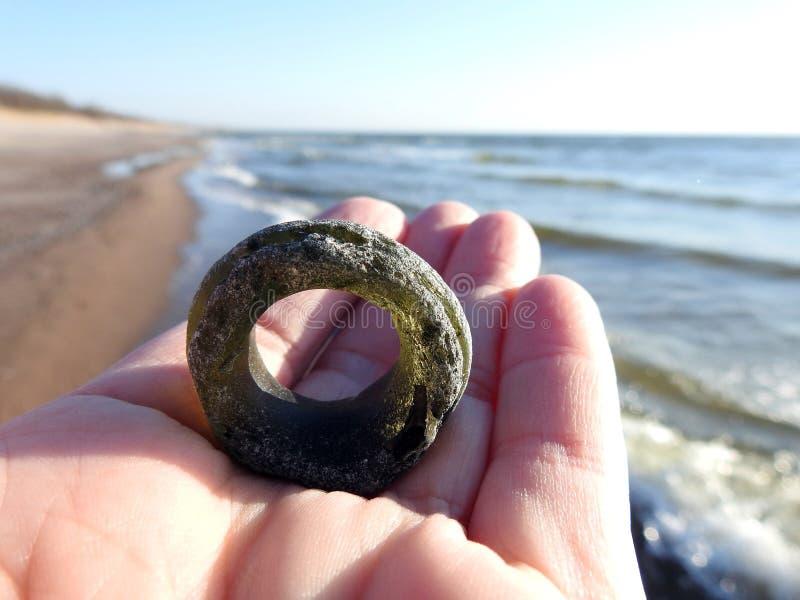 绿色玻璃圆环喜欢在波罗的海海岸,立陶宛的妇女手上 库存图片