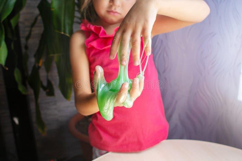 绿色相反软泥流程下来从儿童的手 库存照片
