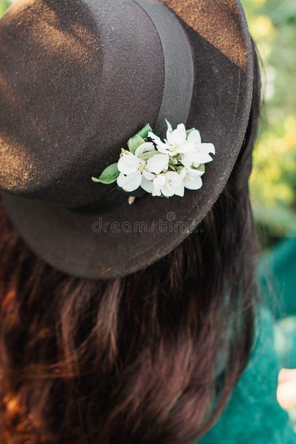 绿色礼服和黑帽会议的少女 免版税库存照片