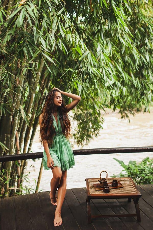 绿色礼服的妇女喝健康茶 免版税库存照片