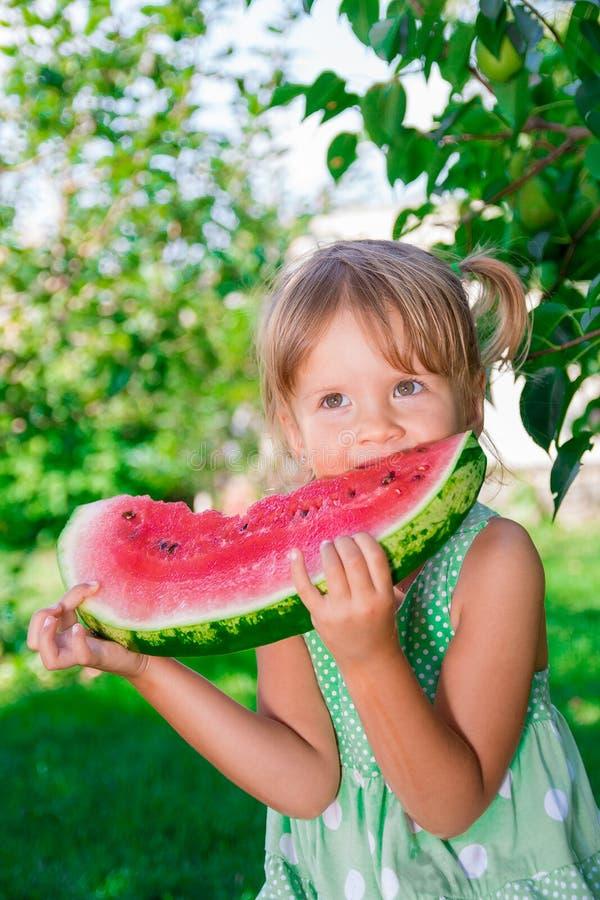 绿色礼服的小女孩吃大切片西瓜的在公园 免版税图库摄影