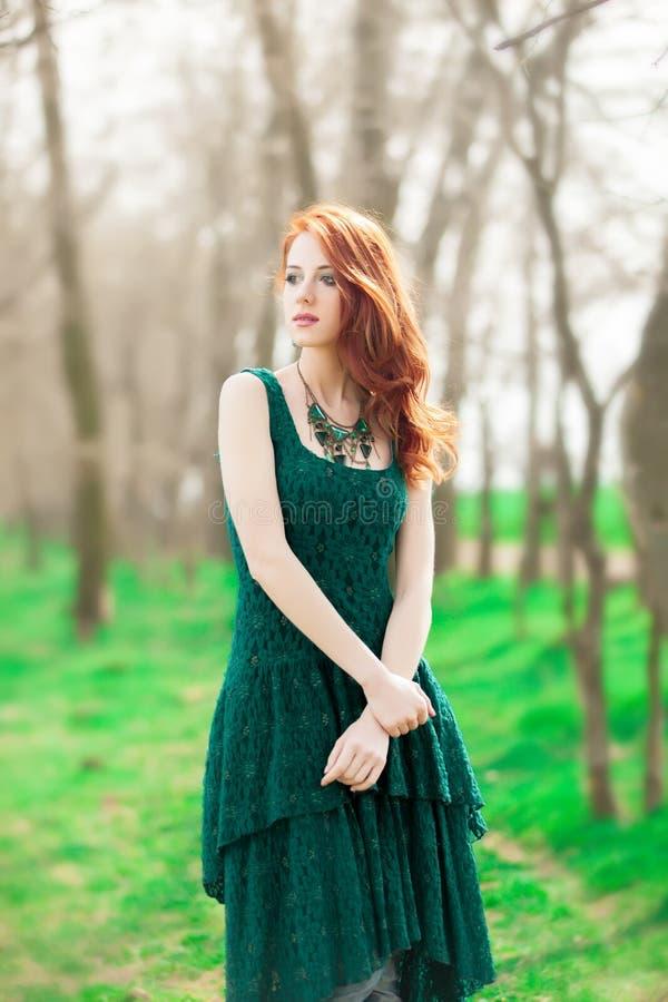 绿色礼服的红头发人女孩在公园 免版税图库摄影