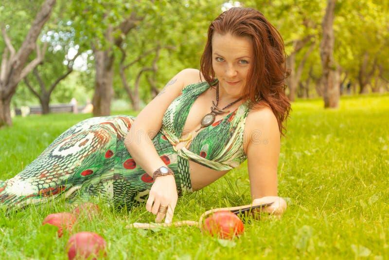绿色礼服看书的俏丽的微笑的愉快的女孩和说谎在草 库存照片