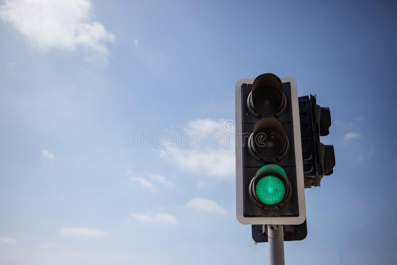 绿色红绿灯 蓝天有少量云彩背景 关闭在看法, copyspace下 免版税库存照片