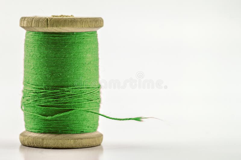 绿色缝合针线卷轴或短管轴在白色的 浅 库存照片