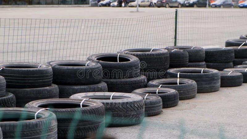 绿色网栅后方混凝土路面上的旧黑轮胎安全屏障 媒体 很多 库存照片