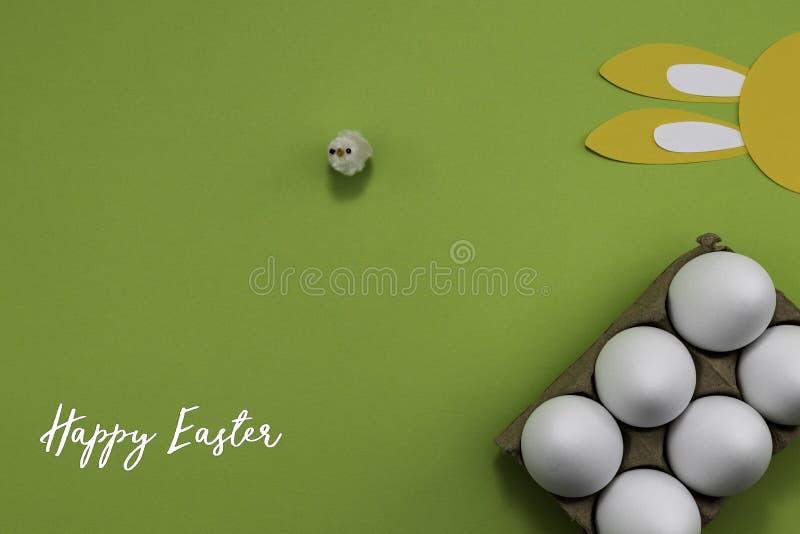 绿色背景下彩蛋和纸兔耳朵的复活节快乐 免版税库存图片