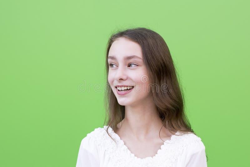 绿色背景的年轻微笑的妇女 免版税库存照片