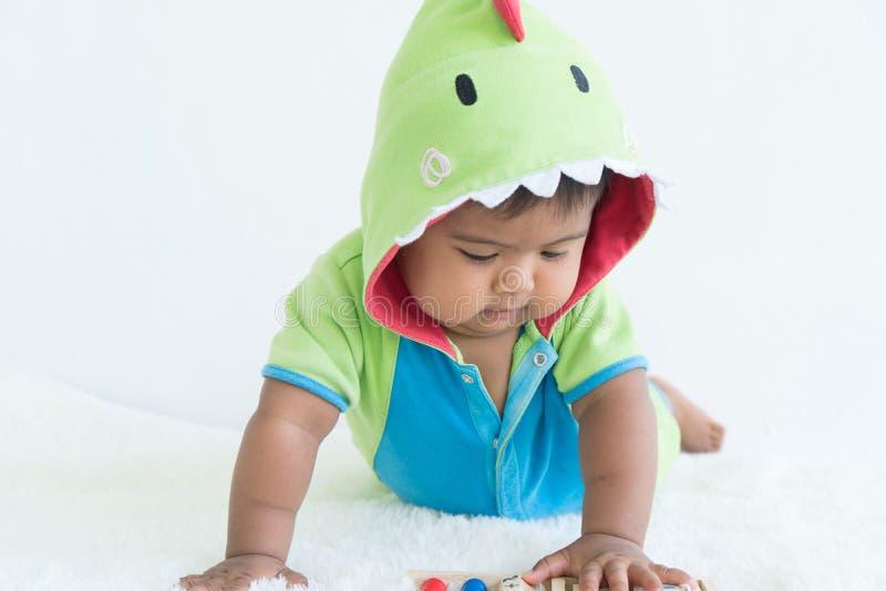 绿色舞会服装的逗人喜爱的矮小的亚裔婴孩 免版税库存照片